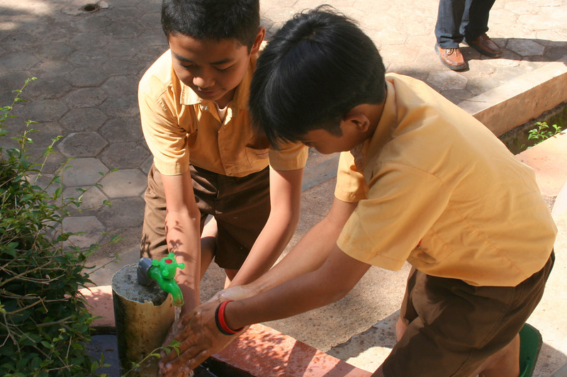 Students washing their hands using the taps and water supply provided by IRD