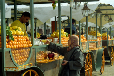 A local enjoys some of the orange juice that is for sale on the Djamaa El Fna - Marrakesh Morocco ... March 7, 2005 ... Photo by Heather Page