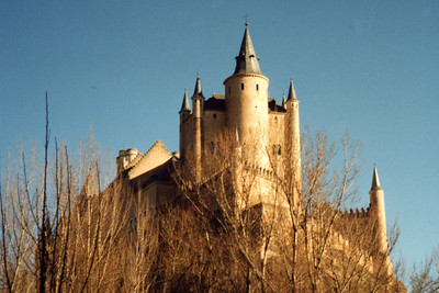 The Alcazar of Segovia.  This is one of the castles Disney used to produce its fairy-tale castle.  Rising out on a rocky crag above the confluence of the rivers Eresma and Clamoresnear the Guadarrama mountains, it is one of the most unique castle-palaces in Spain by virtue of its shape - like the bow of a ship. The Alcázar was originally built as a fortress but has served as a royal palace, a state prison, a Royal Artillery College and a military academy since then. - Segovia, Spain ... March 2003 ... Photo by Rob Page III