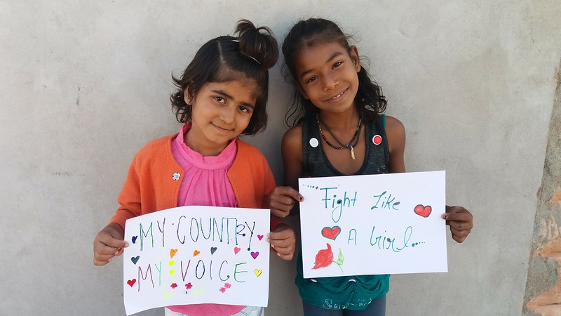 two girls with signs at Sambhali Trust