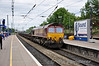 66207 passes through Ealing Broadway with a train of empty steel wagons. Sun 15.05.11