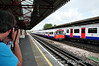 An enthusiast photographs a passing 73 stock train at Stamford Brook. Sat 09.08.14