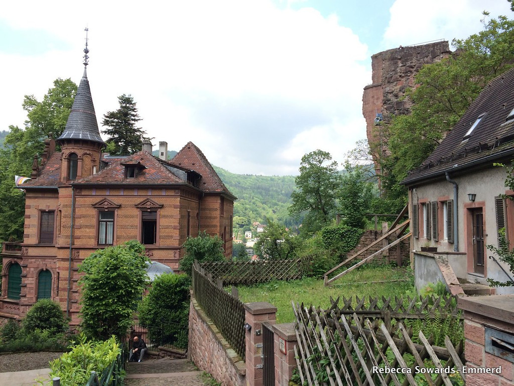 Beautiful homes, with a crumbling castle tower in the background.