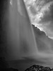 Iceland, Seljalandsfoss - Curtains of water from beneath the falls, black and white
