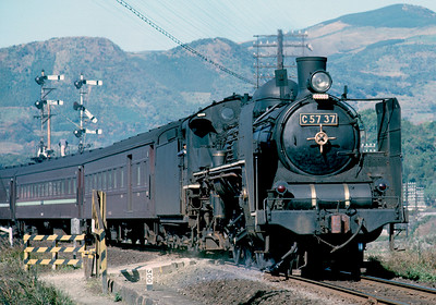 Circa 1963.  The C57 were graceful little engines. It has been a long time, but I believe this is a Sasebo to Nagasaki local approaching the junction at Haiki where the branch to Sasebo joins the mainline to Nagasaki. It was all steam around Sasebo in 1963, even though the bullet train line was under construction out of Tokyo.