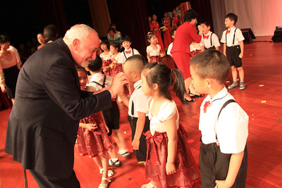 Ron Strauss participates in a kingergarten graduation tradition in which educators paint a red dot on each child's forehead to signify the knowledge that they have gained. Beijing Royal Schoo, May 31, 2011.