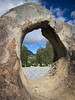 Norway, Horndøla Bru - Three sheep visible through a round hole in a rock