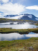 Norway, Jotunheimen - Two lakes and distant mountain reflecting blue and clouds in sky