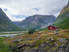 Norway, Gjerde - Red cabin in large glacial valley on edge of river