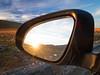 Norway, Jotunheimen - Sun setting in side view mirror in car