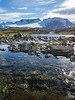 Norway, Jotunheimen - Lake with rocks and distant mountain