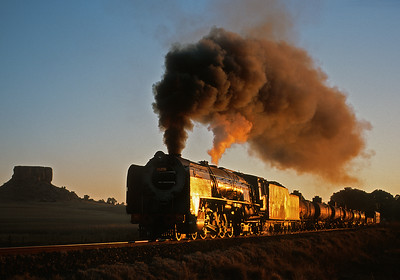 May 28, 2007.  The last light glints off a Class 25NC passing by the butte at Sekonyela, near Ficksburg.