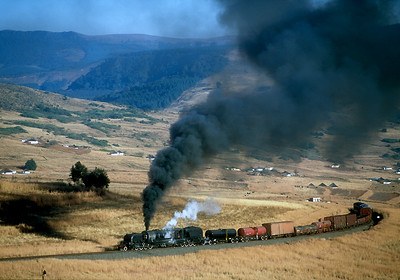 A GMAM Garratt heads a special mixed train on the steeply graded Natal line that started as a through route from Durban to Capetown, but was never completed due to the rough country. The countryside is dotted with the typical round huts of the Zulus. Over 120 GMAM's served on South African Railways, with the last built in 1958.  After Mjila on the climb to Donnybrook.  June 4, 2007.