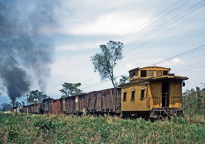 March 1971.  A freight heads up the hill from Santa Maria to Palin with a mid-train helper.  The helper base was Escuintla, but the grade started west of there and helpers were often put on at Santa Maria.  East from Santa Maria the grade gradually increased reaching 3 percent approaching Escuintla.  Out of  Escuintla it quickly increases to 3.6 percent with the steepest section of 3.7 percent near the summit.
