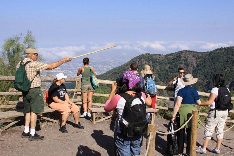 The class stops at a scenic overlook to orient themselves within the Italian landscape on the walk up to the caldera of Mt. Vesuvius .