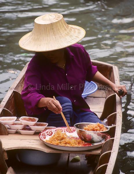 Woman in Prow, Damnoen Saduak Floating Market, Ratchaburi, Thailand, Southeast Asia,