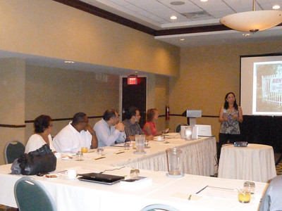 Zulma Rodriguez Monge of Baxter welcomes attendees. Baxter paid for the room for the day, and many of the logistics.