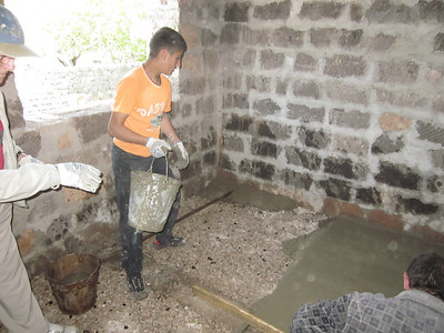 11 05-10   Karen pours concrete for the floor of his house bucket by bucket. LF