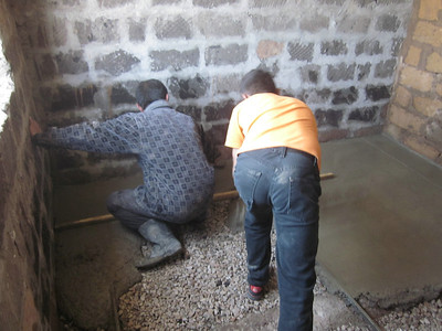 11 05-10  Karen works alongside a skilled mason for making the wet concrete into a finely finished floor.  LF