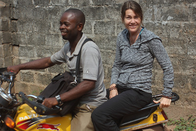 Leslie O'Tool hitches a ride with Ben-Geedeon Mosepi of The Fuller Center school in Bolomba.
