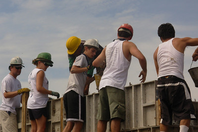 10 03 Team of students from U.S. hard at work pouring buckets of concrete to make a wall for a house. mb
