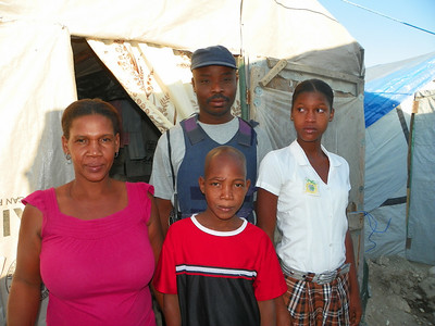 2011 03-18 Rigaud Menes & Jeannelle Marcelyn Menes This family is standing in front of their tent.  Rigaud works as part of the security force for the camp.  Fabienne (pictured) is fourteen years old.  Johnley is 9 years old.  Only Fabienne is able to go to school due to financial reasons.  Because the tent is too small to accommodate all of their children, 2 other children (not pictured) have to remain in the countryside.  Jeannelle sells buckets and 2nd hand clothes when opportunities come her way.  She also cooks food to sell as retail.  .  Jonny Jeune