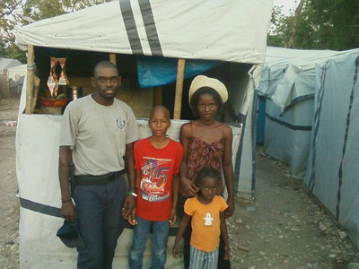 2011 03-18 Antoinier & Cynthia Chaperon Chery This family is standing in front of their tent.  They added an addition to their tent to create a shop where they sell dry food, spices, eggs, beans, etc.  Antoinier also works as part of the security force for the camp.  Frantzie (pictured) is ten years old.  Nerla is 4 years old.  Only the boy is able to go to school due to financial reasons.  Because the tent is too small to accommodate all of their children, 2 other children (not pictured) have to remain in the countryside.  Jonny Jeune