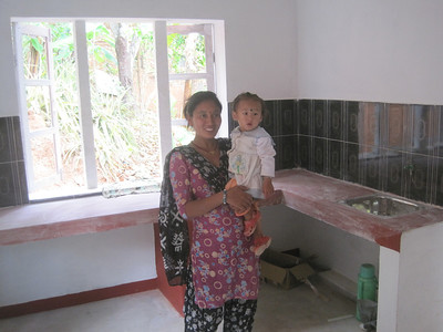 Mother and child in their Fuller Center home's kitchen.