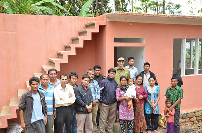 Nepal - One of our finished homes with the family and volunteer local leaders. The homes are built with a reinforced concrete roof that is capable of holding a second floor - which is typical for Nepali families.