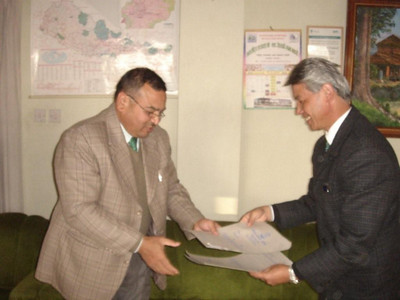 08 12-18 Bajracharya and Tamang exchanging agreement paper. jpg