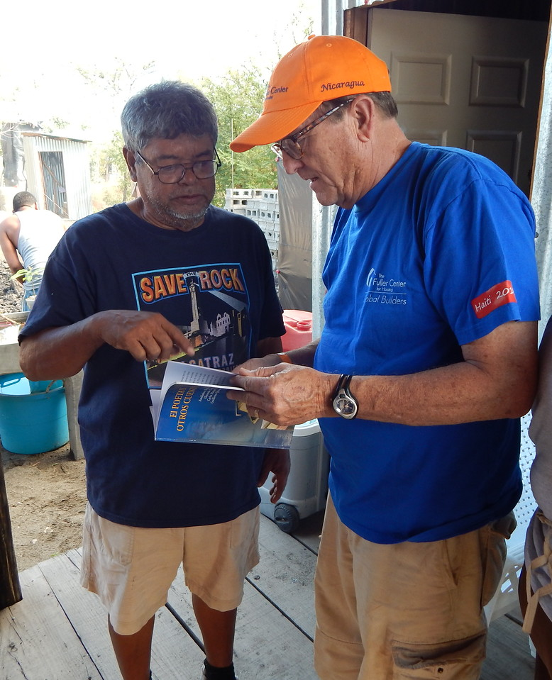 Guillermo, a homeowner partner, shows David Snell a portion of a book on construction that he wrote.