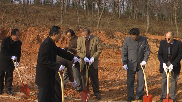 09 11-11 David Snell (middle) has a moment of reflection at the significance of shoveling dirt for first 50 houses...shoveling in hopes of building trust and peace while building houses to relieve overcrowded living situations.