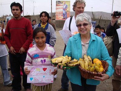 09 07 The residents of La Florida threw a welcoming party for the 8-member team. There were gifts, Peruvian music, and dancing. Margaret Favre is holding 2 of the gift fruit baskets presented by the villagers.  j&mf