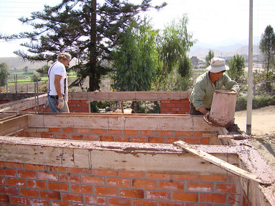 09 07  Professional masons Robert Dillehay and Pancho top walls with concrete to provide a foundation for the roof. The wooden rafters will be anchored on only one side so that the roof slides slightly during an earthquake. j&mf