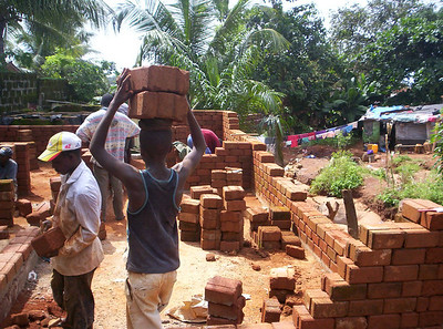 10 09-08  As walls go up on first house, notice the old dwelling off in the background. The contrast between the old and the new is striking. as-b