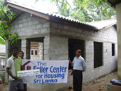 10 October - Two Fuller Center staff hold banner in front of the Roshan Sudarshana home. A room and roof were build so the family can finish out the house with their savings. ranajan
