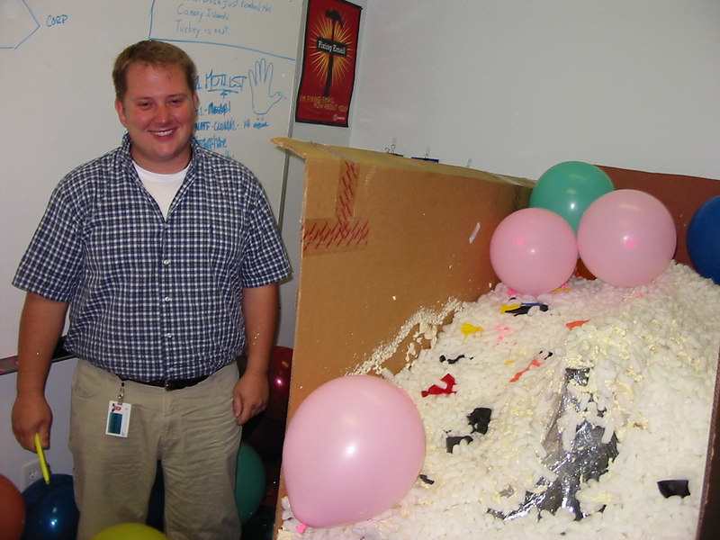 Once I got past enough balloons to tear off some of the cardboard wall around my desk, I discovered the entire desk and everything on it was wrapped in plastic wrap, covered in foam peanuts, and glued together with five of those cans of insulating foam.