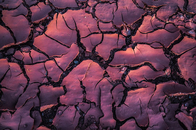 Cracked mud glowing from reflecting sunlight off a canyon wall