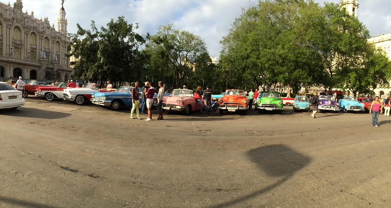 Taxis waiting for hire.  Most of these cars have been handed down through generations.  Same way their homes are.