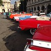 Taxi gathering hoping tourist will hire them for a ride around Havana.