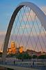 Sun setting on state capital through walking bridge