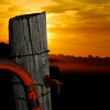 Sun setting on unused fence post