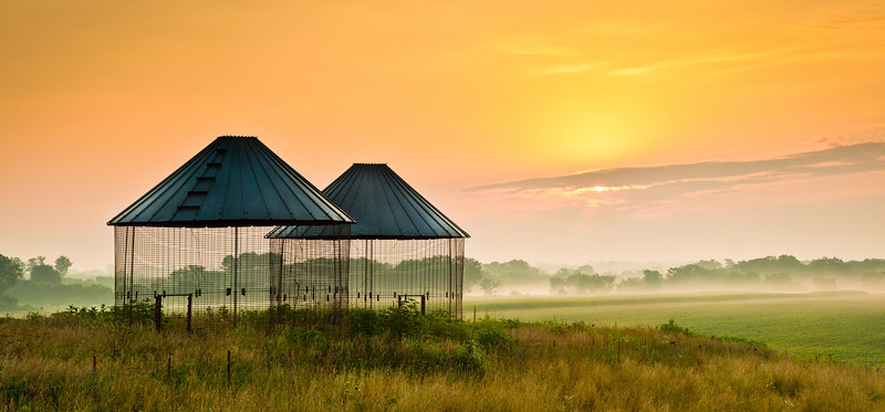 Empty corn cribs and sunrise