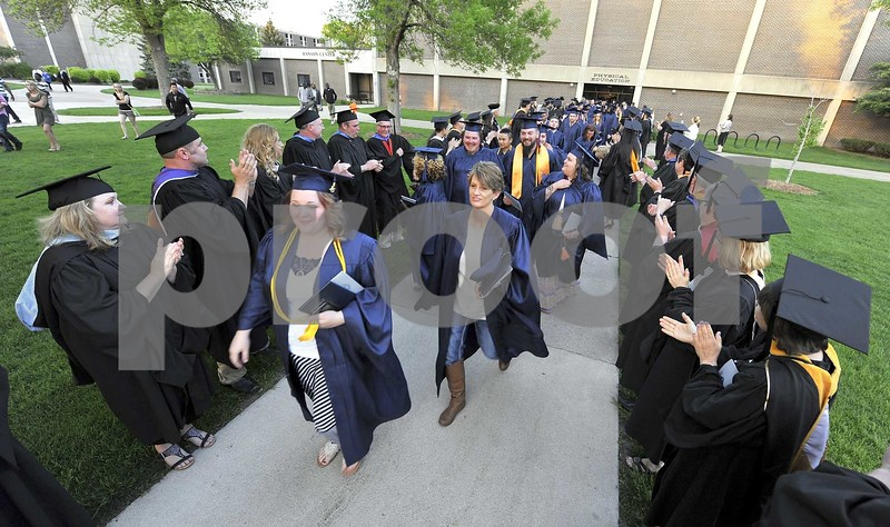 -Messenger photo by Hans Madsen<br /> <br /> After getting their diplomas, some of the 441 graduates who walked across the stage walk through the traditional rows of applauding faculty members as they exit the gym following the 48th annual Iowa Central Community College Commencement Friday evening.