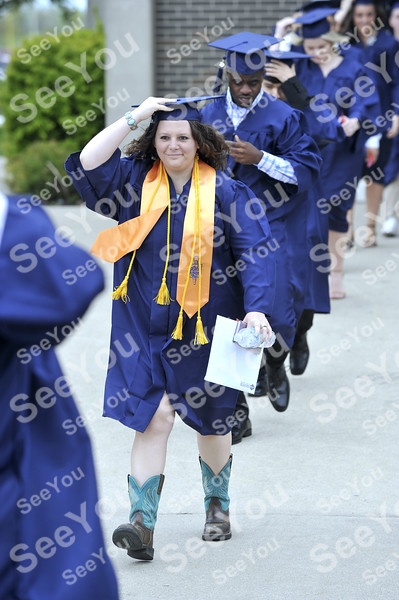 -Messengerr photo by Hans Madsen<br /> <br /> Iowa Central Community College about to graduate student April Connolly holds onto her mortar board Thursday afternoon as she walks toward commencement with about 500 other students.