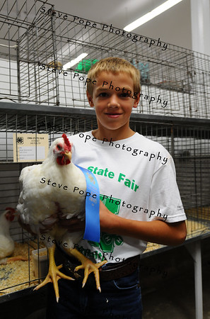 Brian Brenneman, 11, of Parnell, shows is blue-ribbon rooster at the Iowa State Fair on Aug. 8. (Iowa State Fair/ Steve Pope Photography)