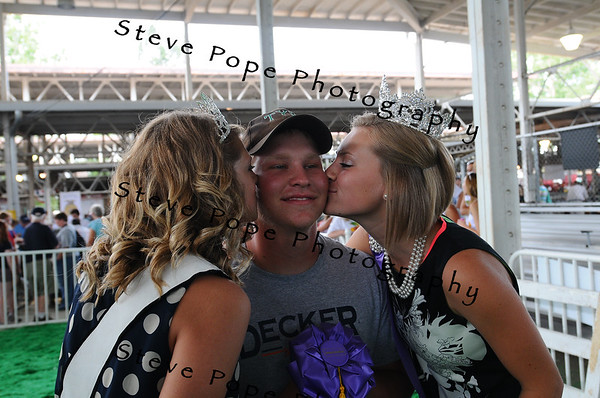 Breanna Branderhorst, Iowa Pork Queen, of Prairie City, (left) and 2012 Iowa State Fair Queen Abrah Meyer, of Readlyn, give a quick kiss to one of the owners of the 2013 Iowa State Fair Big Boar, Jake Meinder, of Buffalo Center, at the Iowa State Fair on Aug. 8. (Iowa State Fair/ Steve Pope Photography)