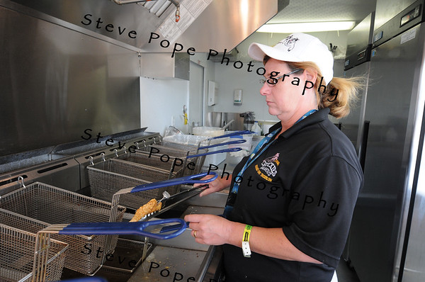 Sandy Cox, of Dewitt, prepares a hand-breaded tenderloin at Chuckie's Famous Breaded Tenderloin stand at the Iowa State Fair on Aug. 9. (Iowa State Fair/ Steve Pope Photography)