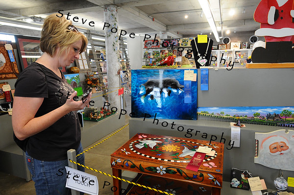 Tonya Gonseth, of Osceola, views fine art on display in the Cultural Center at the Iowa State Fair on Aug. 8. (Iowa State Fair/ Steve Pope Photography)