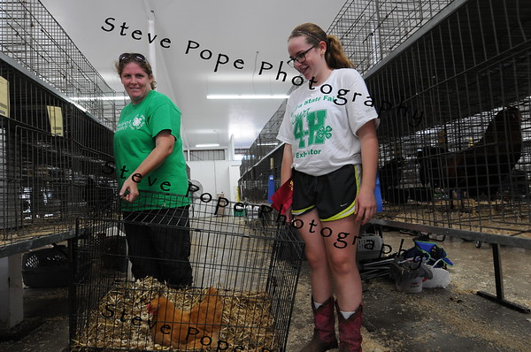 Wendalyn and Josie Burkett, of Winterset, move a chicken cage at the Iowa State Fair on Aug. 11. (Steve Pope Photography/ Iowa State Fair)